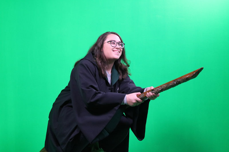 Girl on a broom in front of a green screen